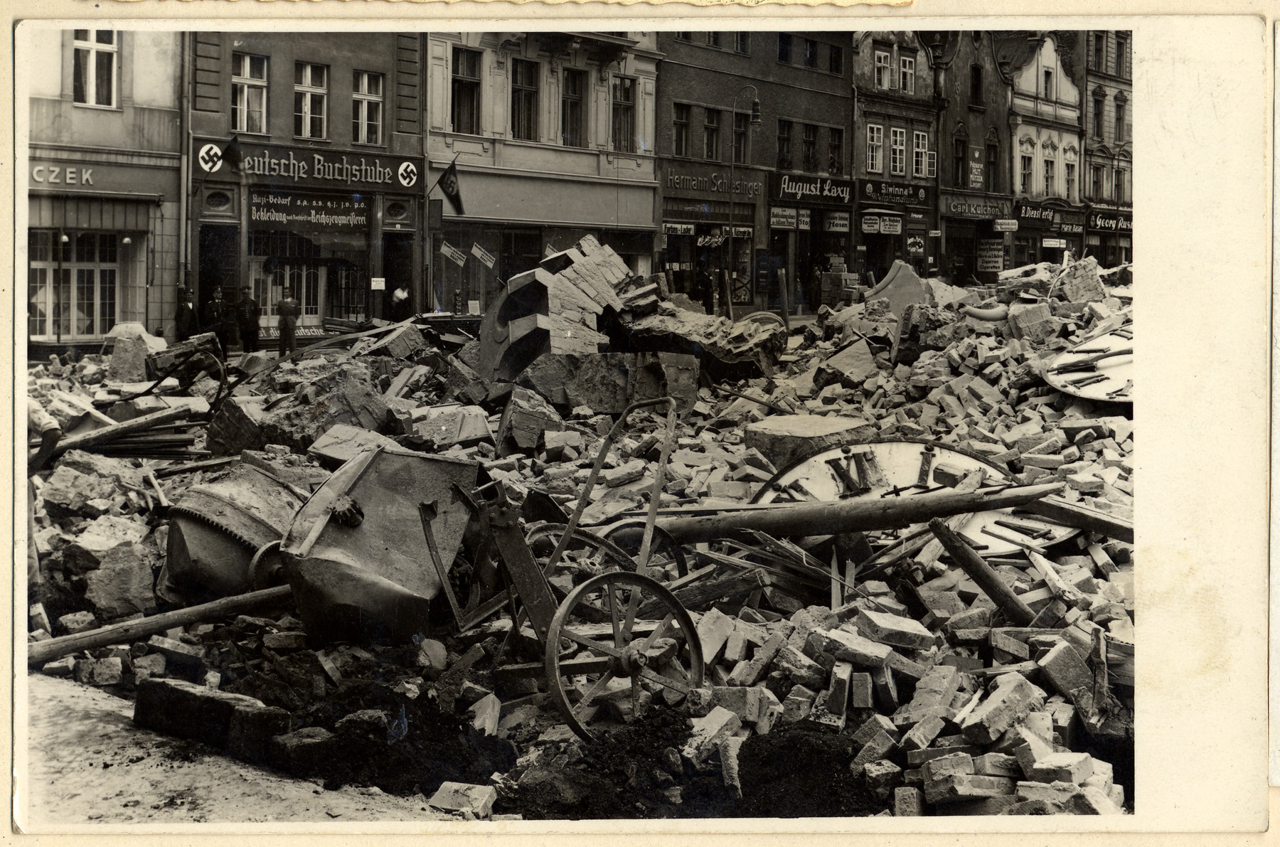 View of a major artery in Oppeln after the collapse of a clock tower.  The shop in the background is a Nazified book store.