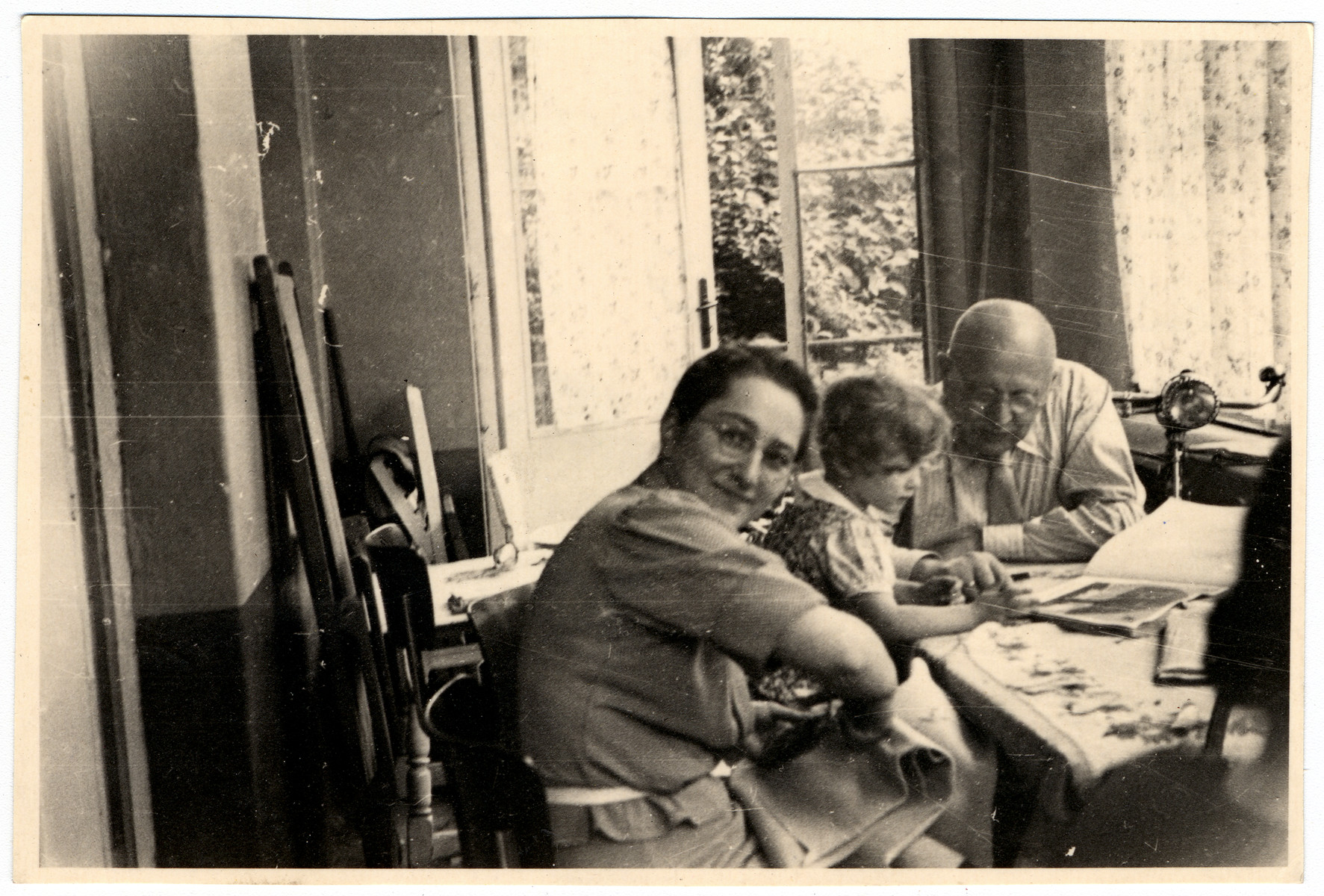 A German-Jewish family gathers around a table and looks at a picture book together.  Pictured from left to right are Marianne Orgler, her daughter Vera and father-in-law Alfred Orgler.  All of them perished in the Holocaust.
