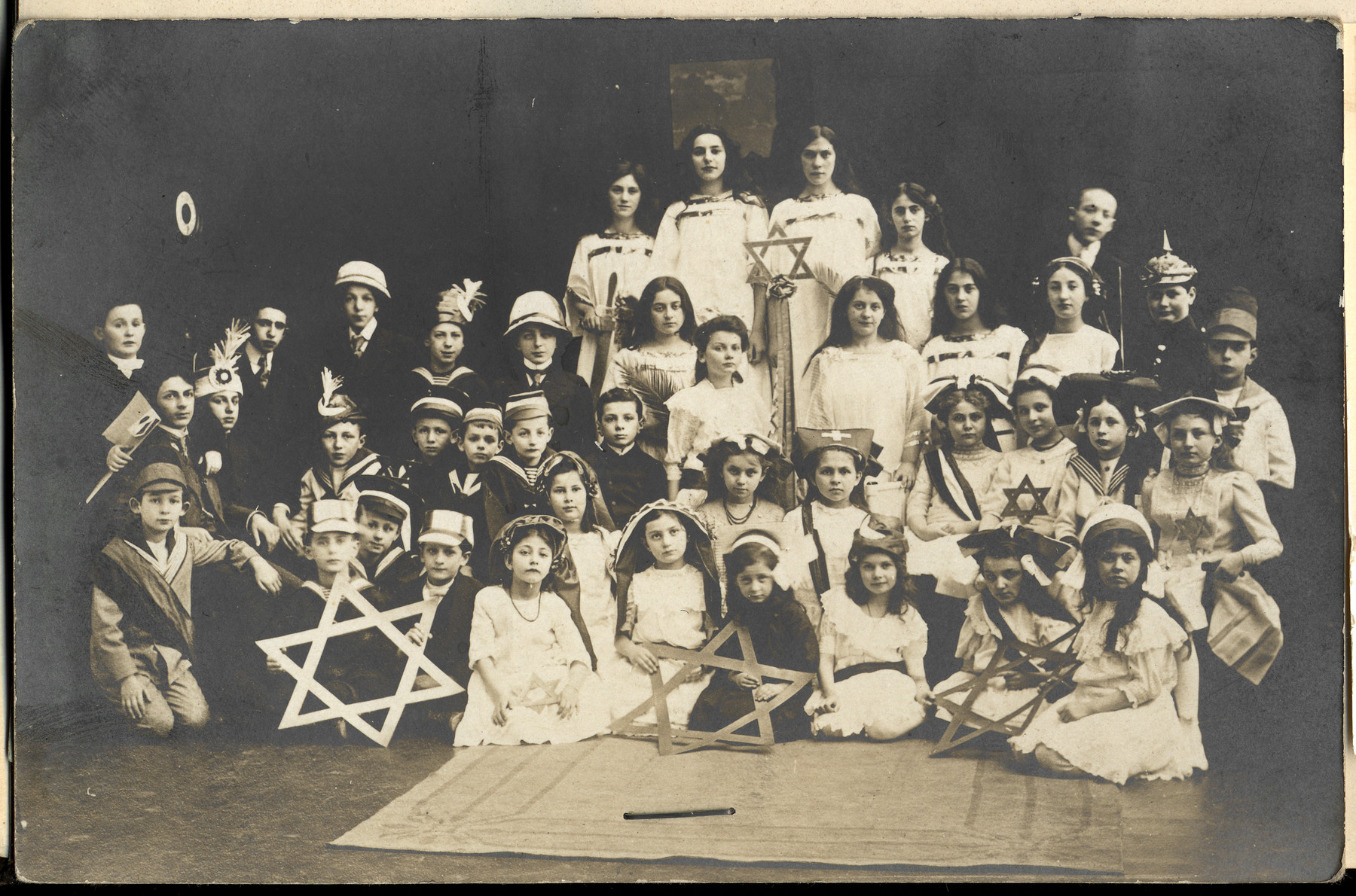 Jewish children dressed in costumes pose for a group portrait surrounded by large Stars of David.  Lotte Orgler is pictured in the second row on the far right.