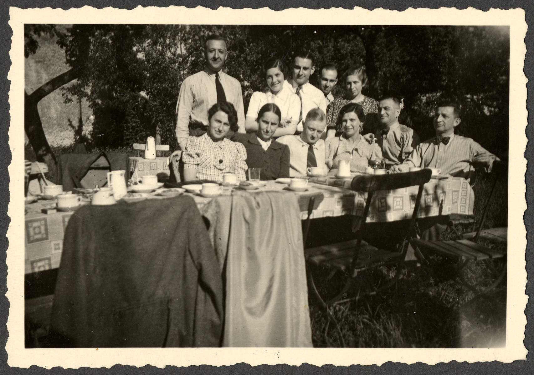 A group of friends enjoys a picnic near Gleiwitz.  Standing left is Dr. Hans Liebermann.  Seated second from the left is Lotte Liebermann.