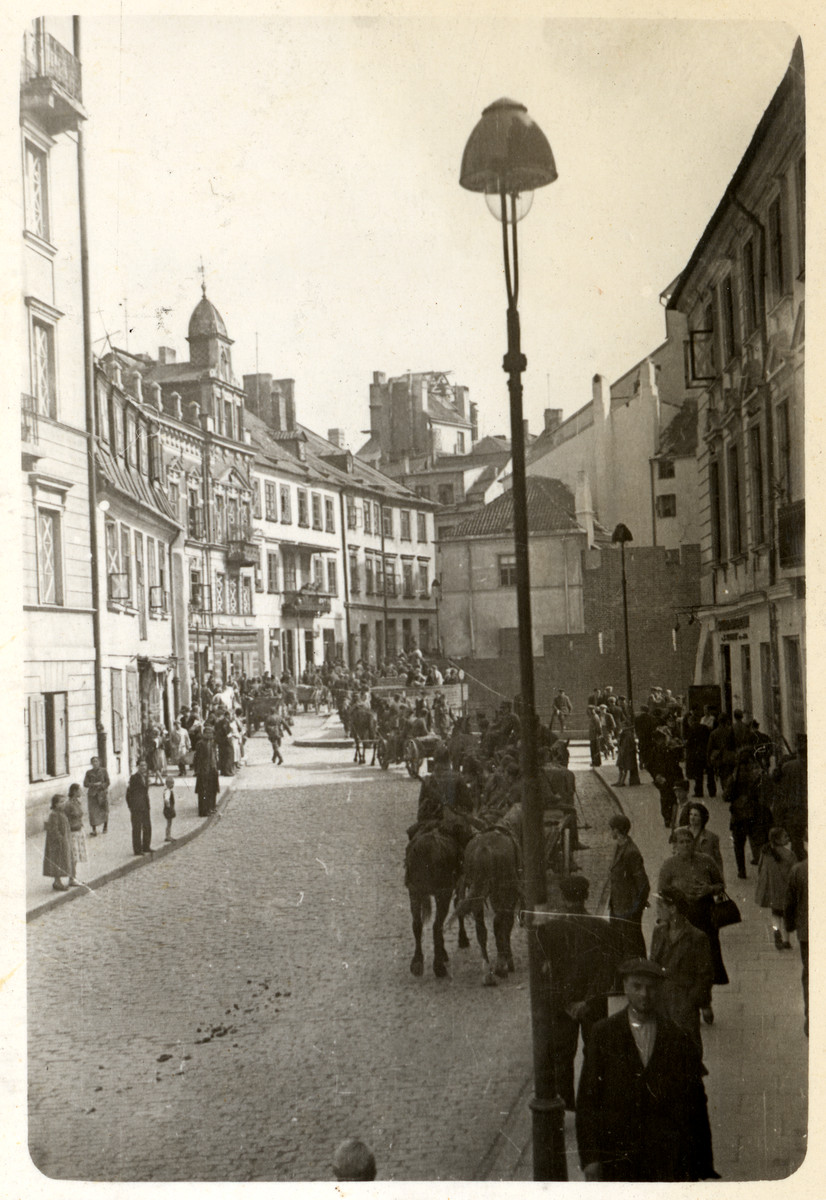 Pedestrians walk down a street in the old town of Warsaw.