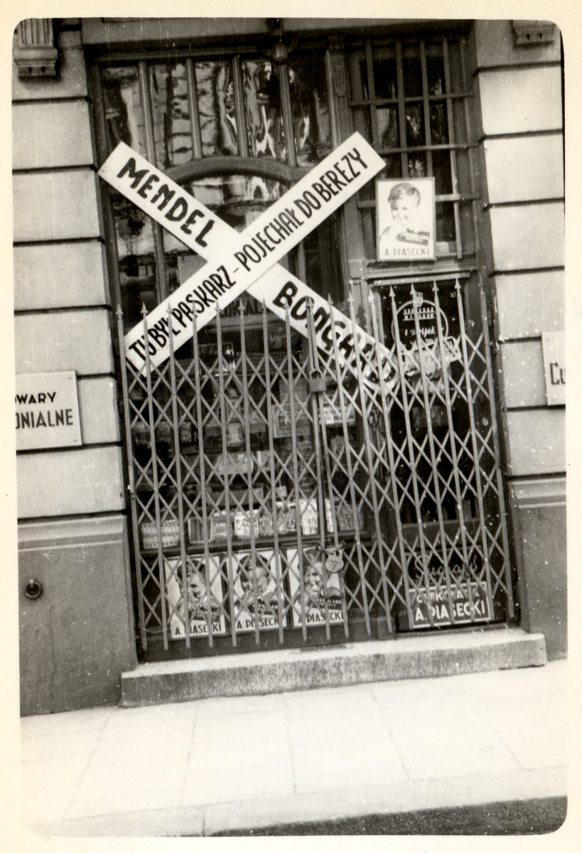 "View of a boarded up store in besieged Warsaw.  The sign outside reads: ""A black marketeer was here - He went to Bereza-Kartuska.""   Bereza - Kartuska was a Polish prison for political criminals that operated from 1934-1939."
