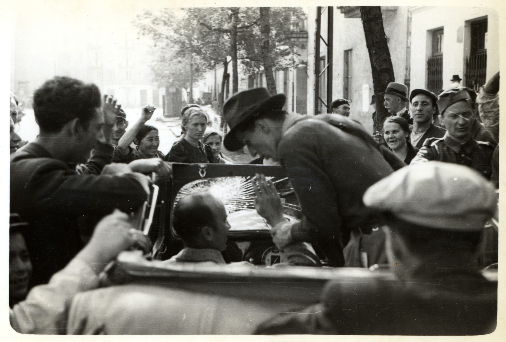 Julien Bryan's driver stops Bryan from waving to a crowd of Polish spectators in besieged Warsaw.