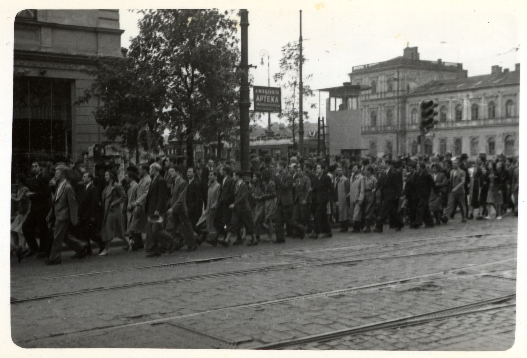 Polish men and women march down a street past a pharmacy in besieged Warsaw.