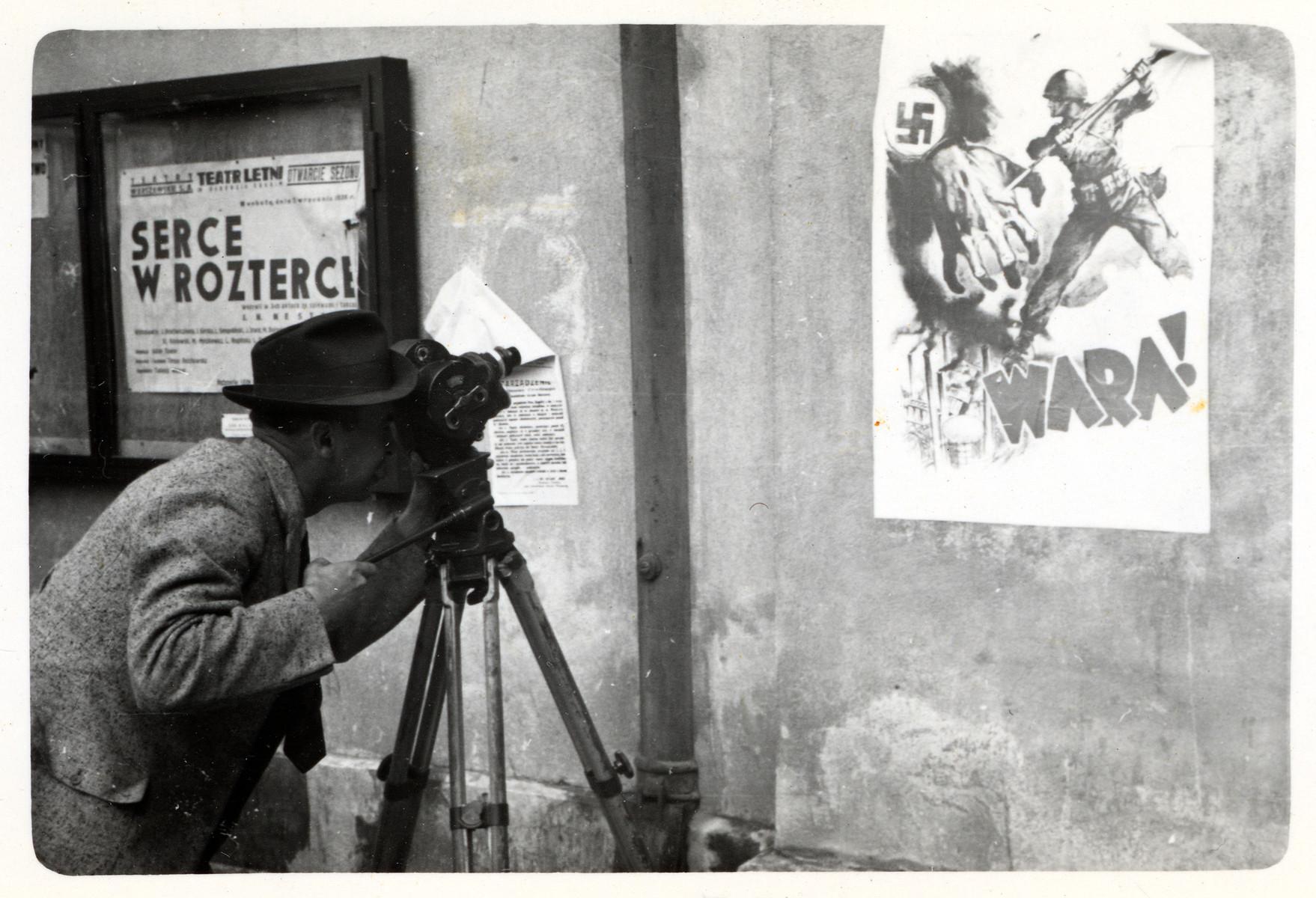 Julien Bryan films an anti-Nazi propaganda poster affixed to a wall in besieged Warsaw.