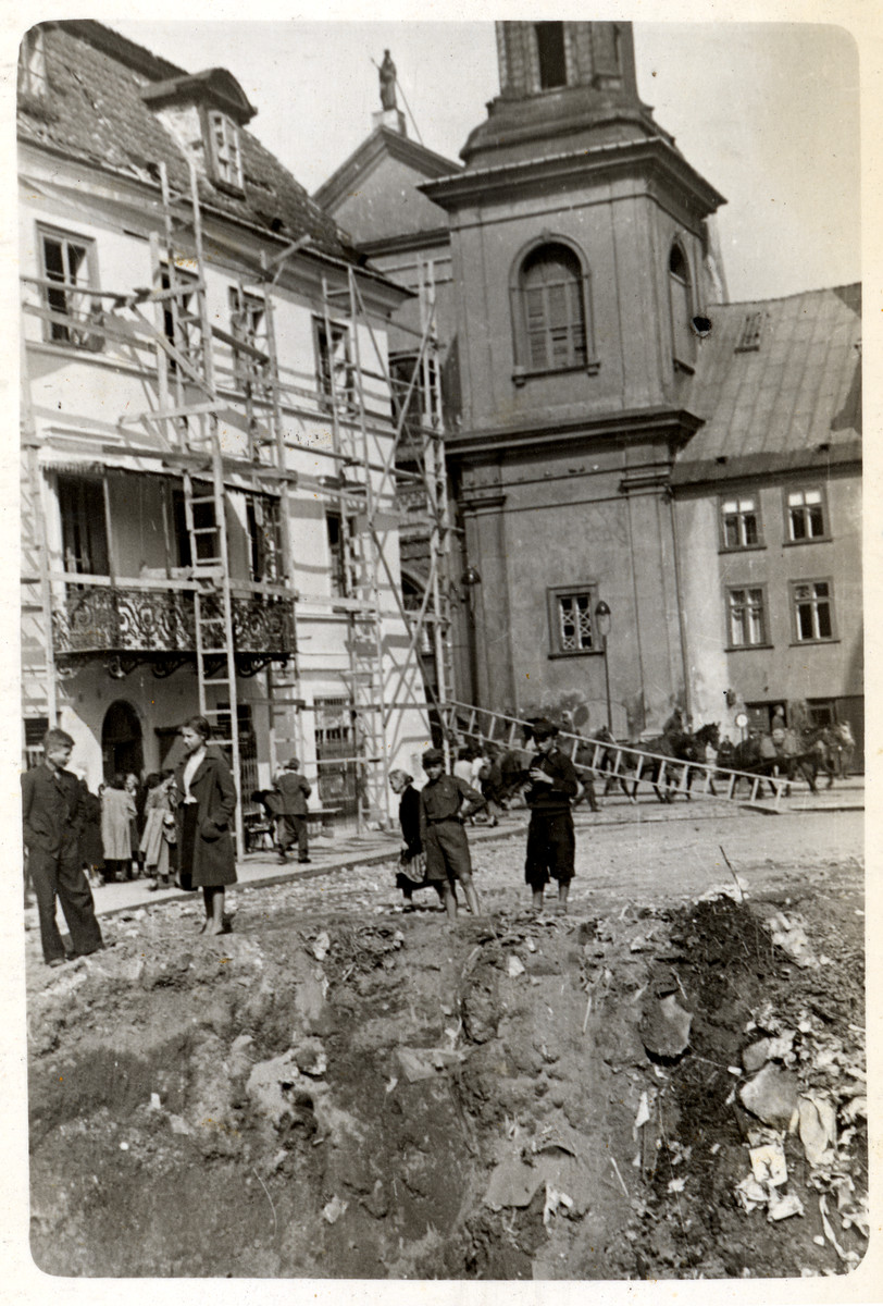 Poles stare at a large hole created from a bombing of a street of beisieged Warsaw.