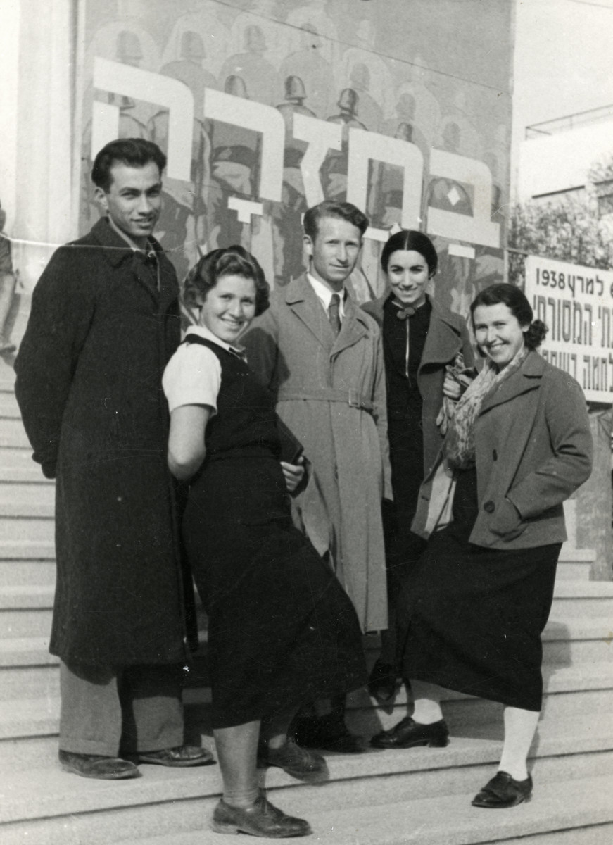"""A group of young adults are pictured upon their arrival in Palestine.   Pictured are siblings Esther (far right), Alex (middle), and Zippora Steiger (left).  The large sign behind them reads """"On Return."""""""