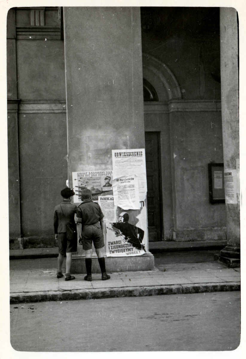 Polish boys look at Polish anti-Nazi propaganda pasted onto columns in besieged Warsaw.