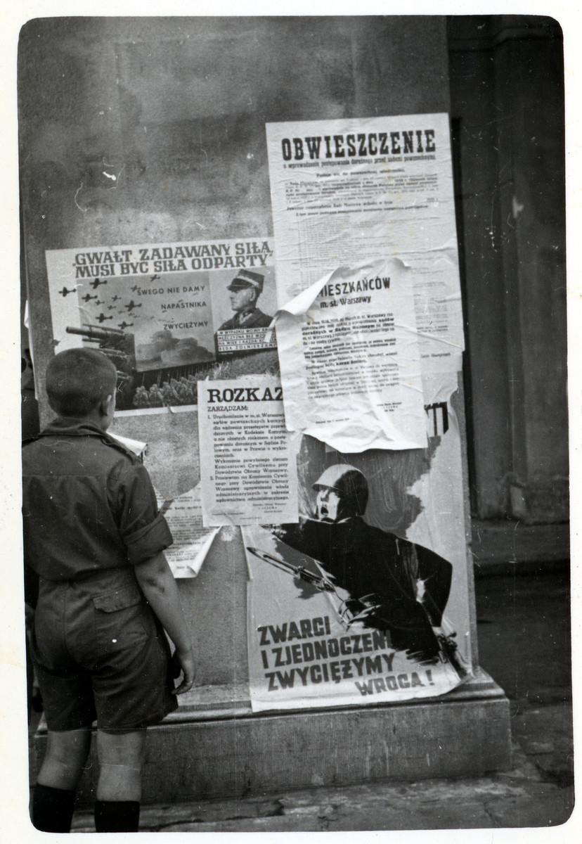 A Polish boy looks at Polish Anti-Nazi propaganda pasted onto columns in besieged Warsaw.