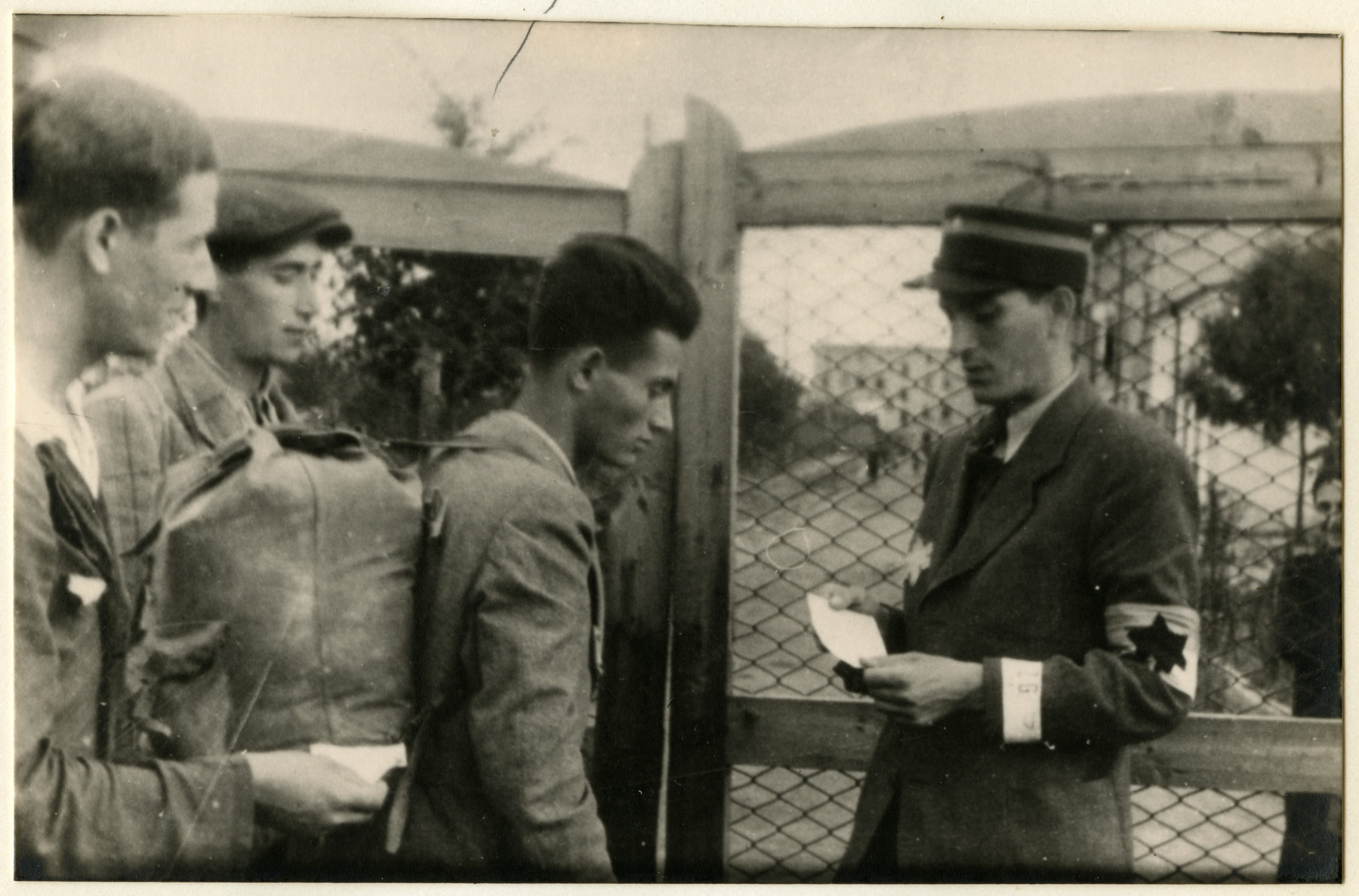 A Jewish policeman checks the documents of several men at the entrance of the central prison of the Lodz ghetto [probably prior to their deportation].