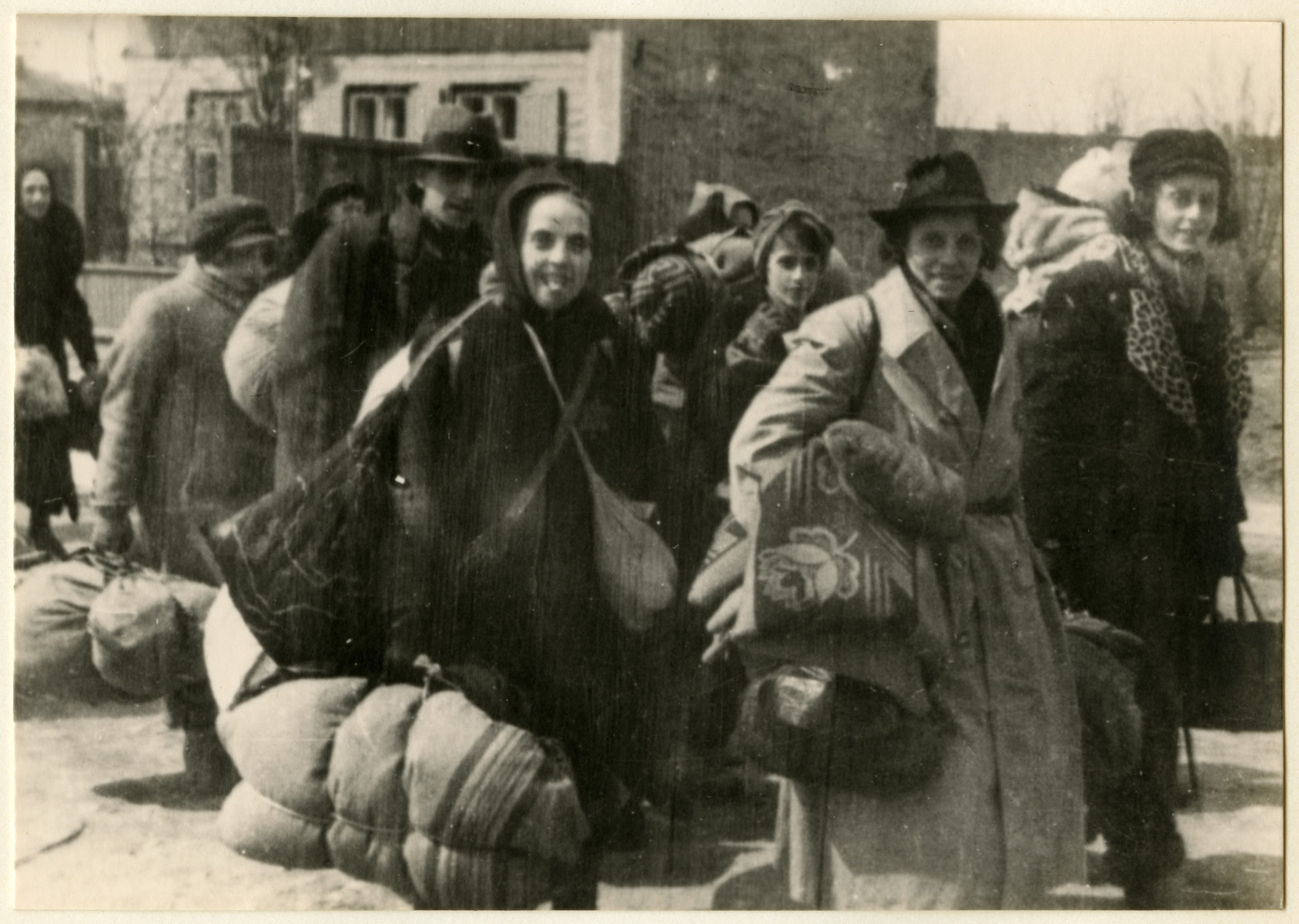 A group of women carrying large bundles march to an assembly point during a deportation action in the Lodz ghetto.