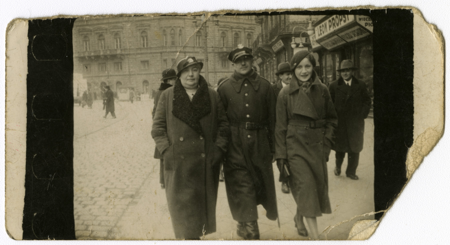 Mrs. Meizels (grandmother of the donor) walks down a street in Lvov with two of her family members.