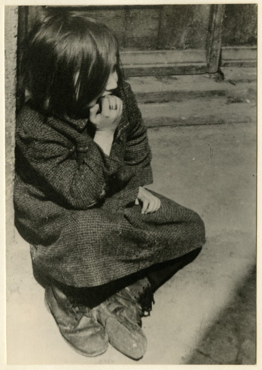 A destitute girl sits on the curb of a street of the Lodz ghetto.