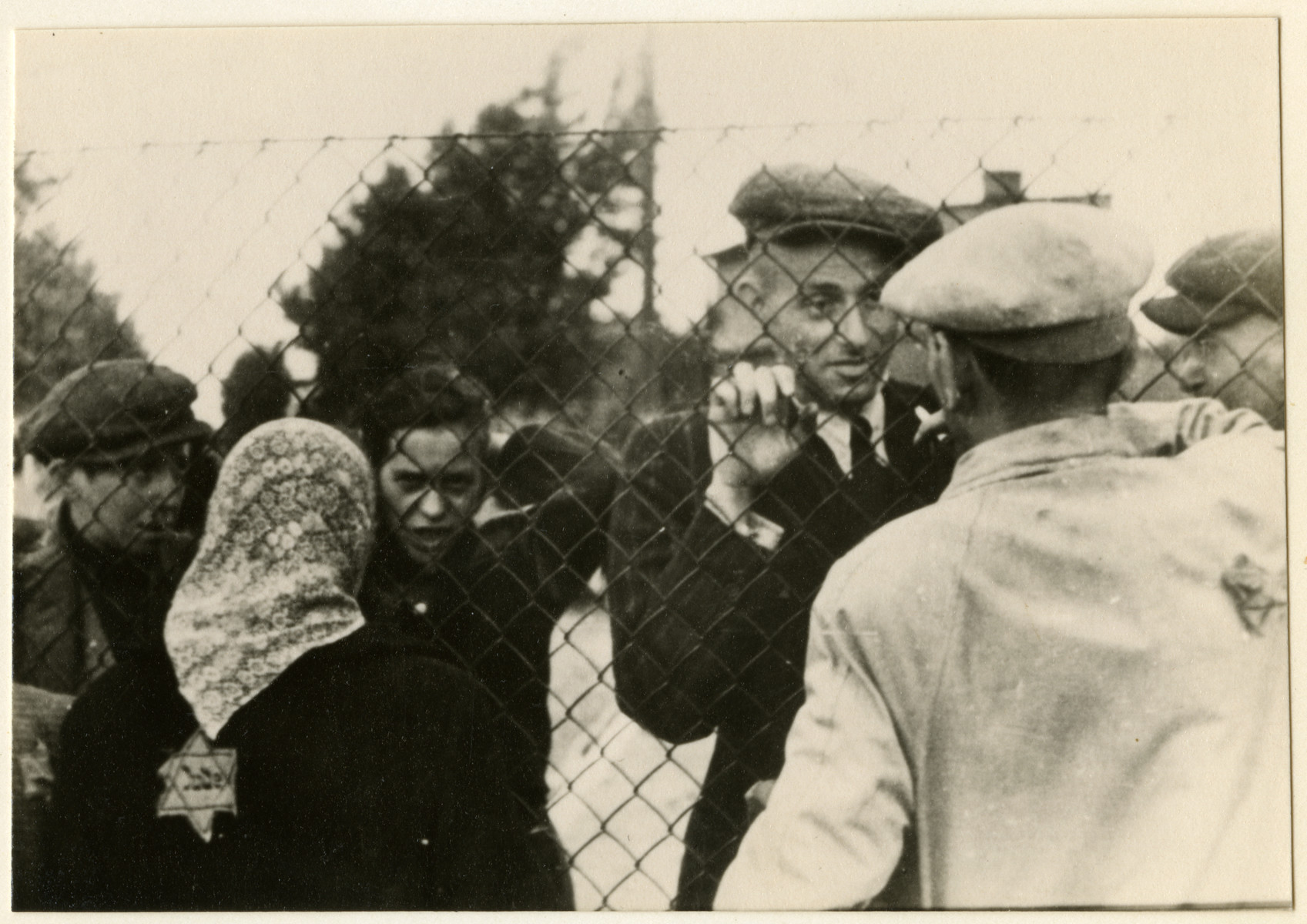 "Jews who have been selected for deportation, bid farewell to their families through the wire fence of the central prison, during the ""Gehsperre"" action in the Lodz ghetto."