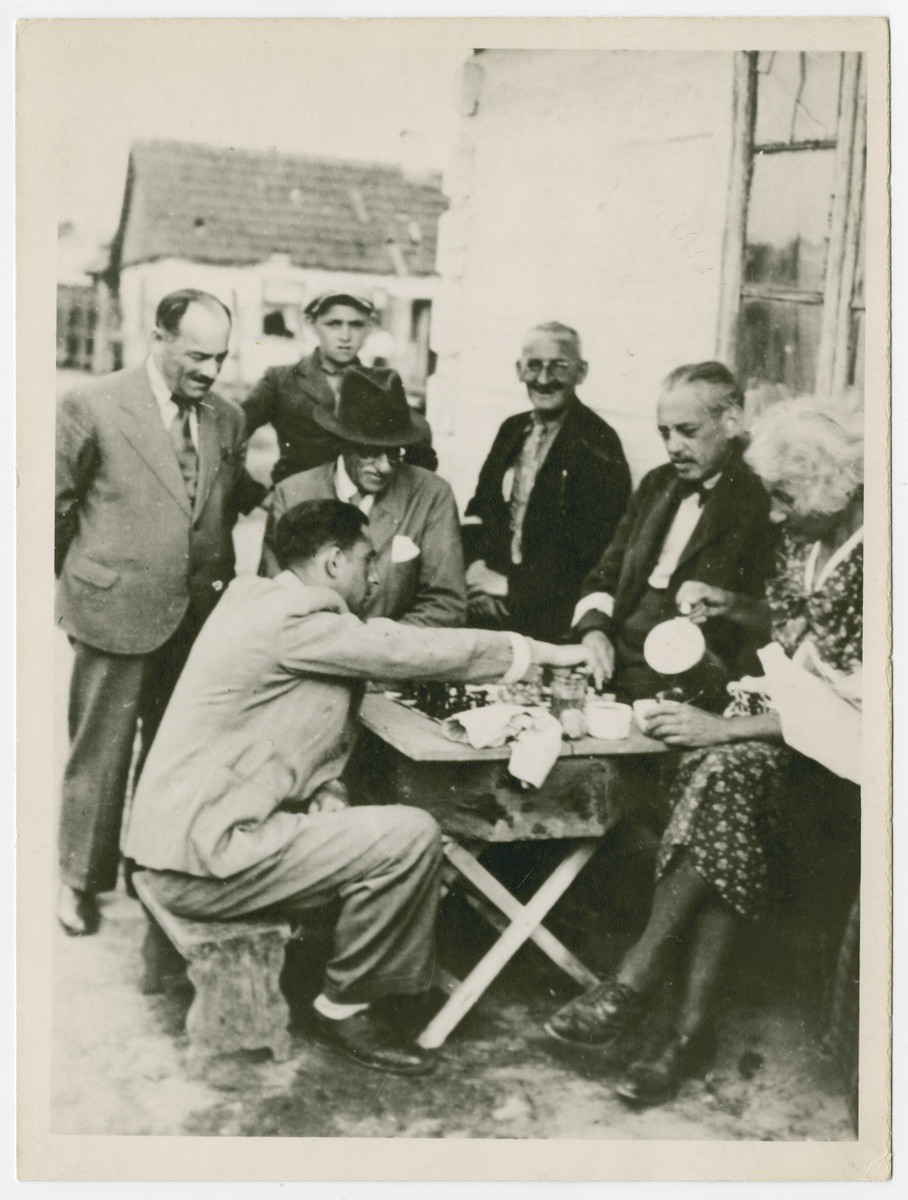 Heinrich Salomon Rosenberg (seated, wearing large hat) and his wife Paula Gewitsch Rosenberg sit around a table and watch a chess game n the Opole Lubelskie Ghetto.