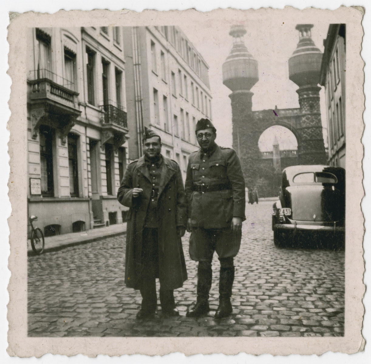 """Leopold Guttman stands next to a friend on a street in Antwerp.  [Note:  Though the photo is labled """"Antwerpen 1939"""" it is also stamped with an official Stalag 10 C stamp.]"""
