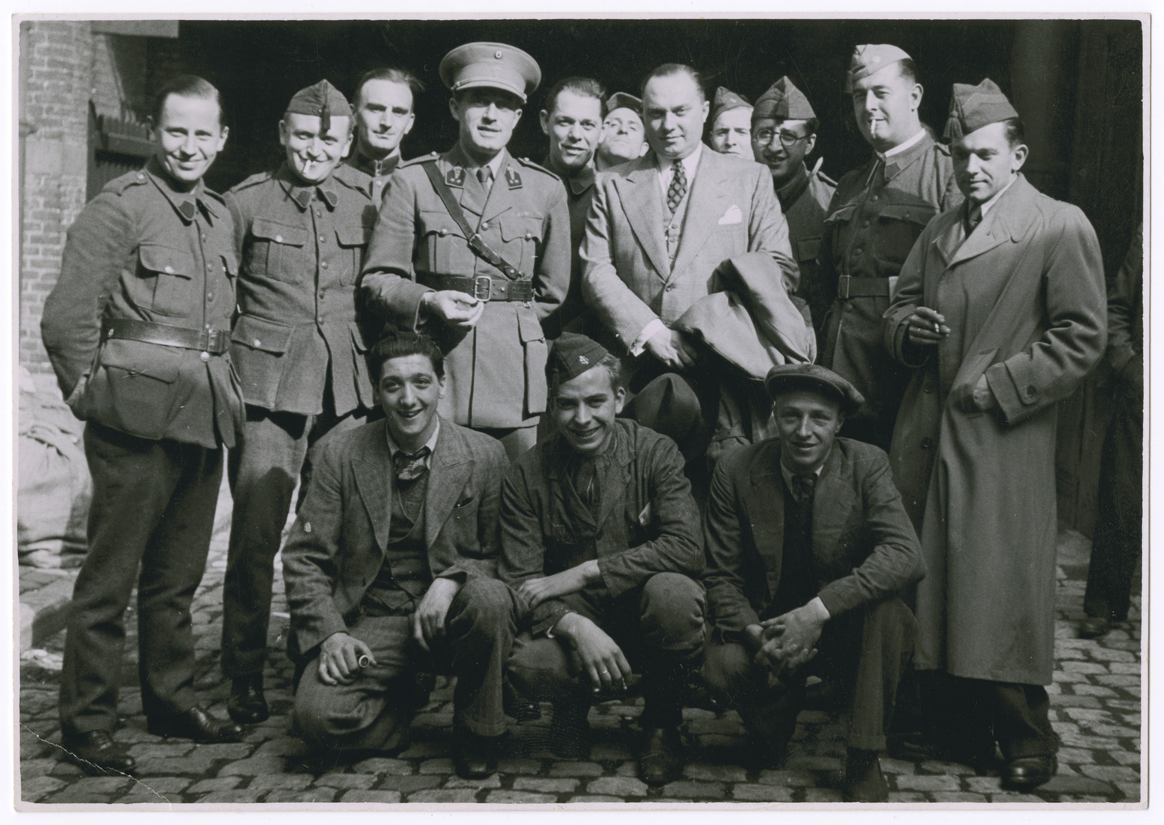 Group portrait of Belgian soldiers and civilians.  Leopold Guttman is pictured standing, third from the right.