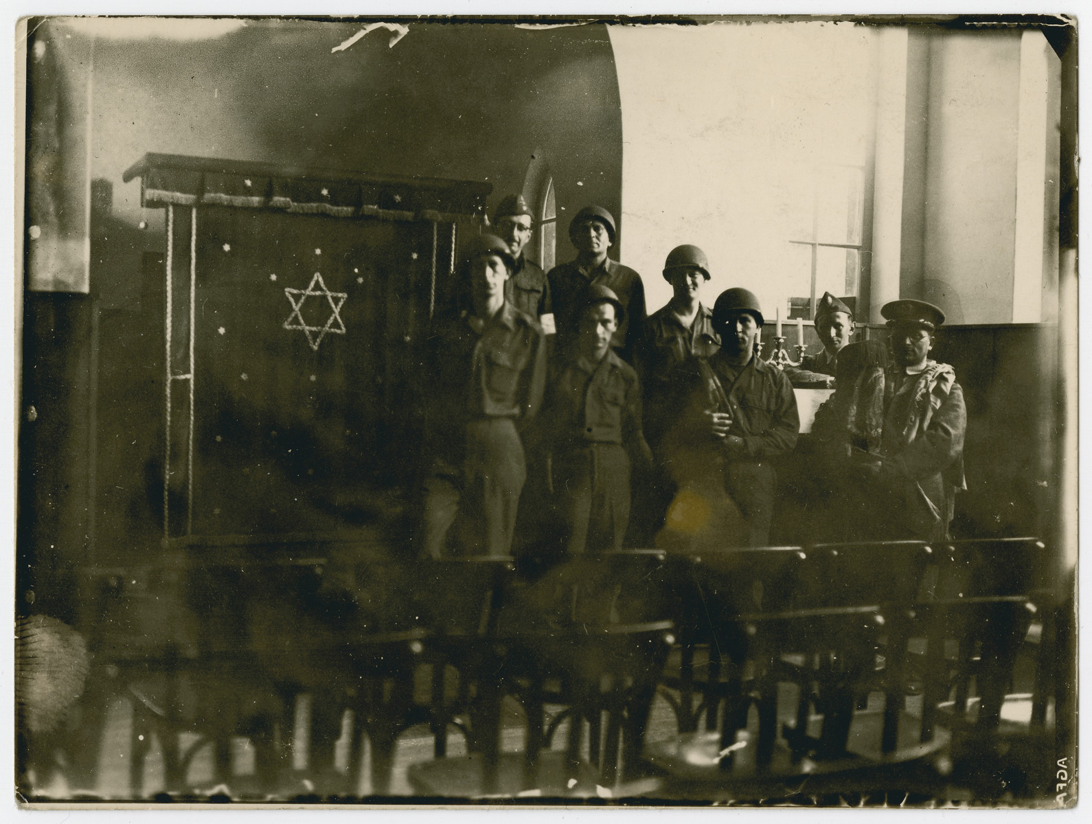 Leopold Guttman, Henry Kahn and other Jewish soldiers pose by the Toah ark in the newly restored synagogue in Wunsdorf after making townspeople repair it and the Jewish cemetery, both of which had been desecrated during the Holocaust.