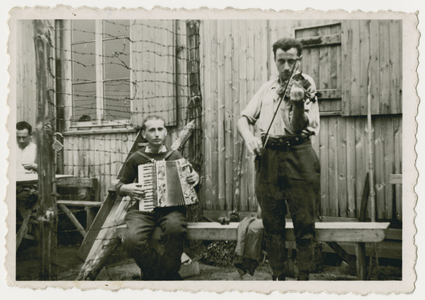 Two Belgian POWs play music outside a barrack in Stalag 10 C.