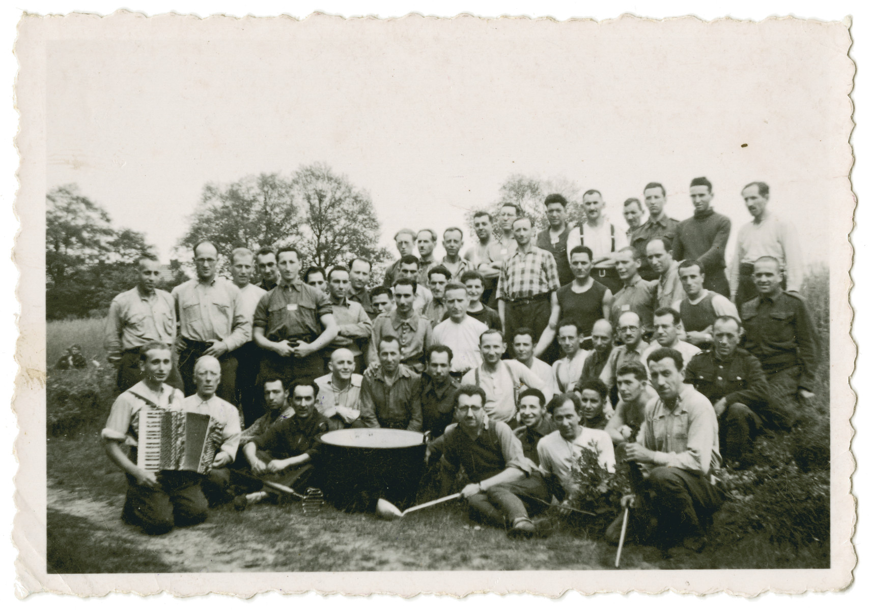 Group portrait of Belgian POWs in Stalag 10 C.  In front is a large pot.  Leopold Guttman is sitting next to it with a large laddle, and another POW holds an accordion.