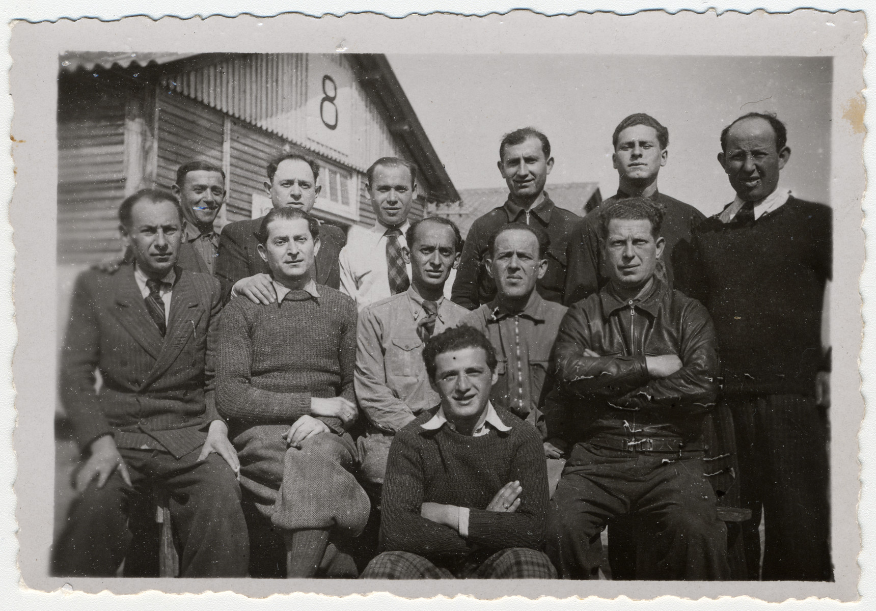 Group portrait of Jewish prisoners outside barrack 8 in the Beaune-la-Roland internment camp.  Among those pictured seated are Jankiel Sztal (second from left), Jankiel Michalowicz (center) and Itzrik Sztal (far right).  Moishe Sztal is standing third from the right.