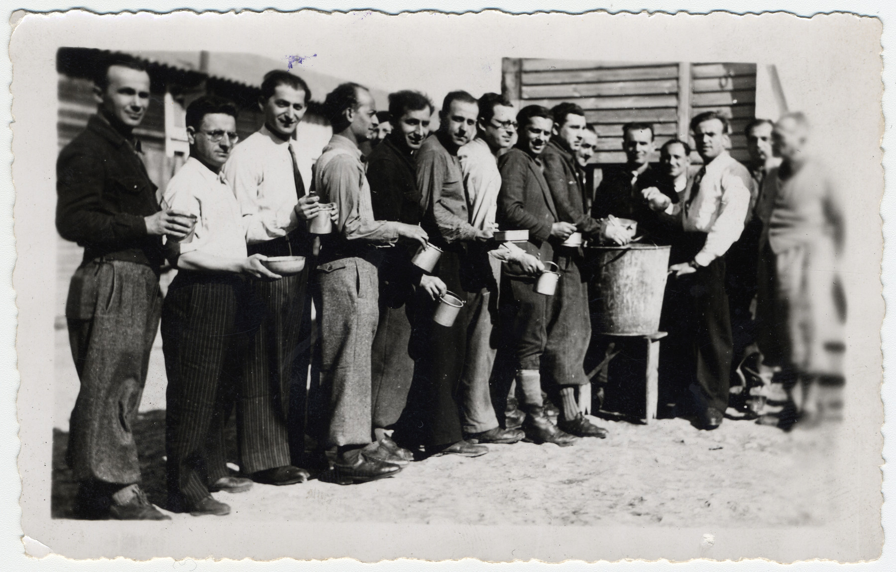 "Prisoners wait in line for their rations in the Beaune-la-Rolande transit camp.  The original caption reads ""Soup distribution.""  Pictured third from left is Chil Jankiel Sztal and fourth from left is Jankiel Michalowicz."