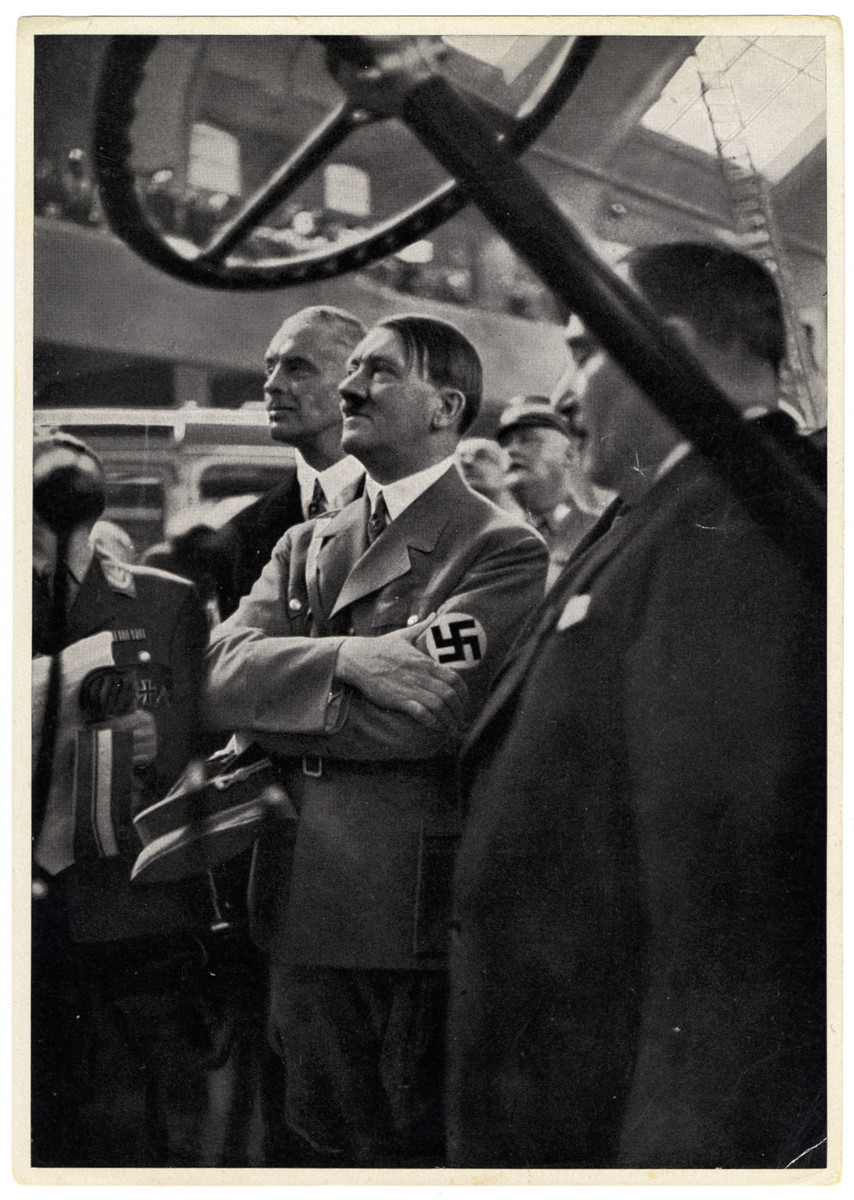 """Caption reads:  """"International Automobile Exibition in Germany 1935: the protector of the auto industry"""" r"""
