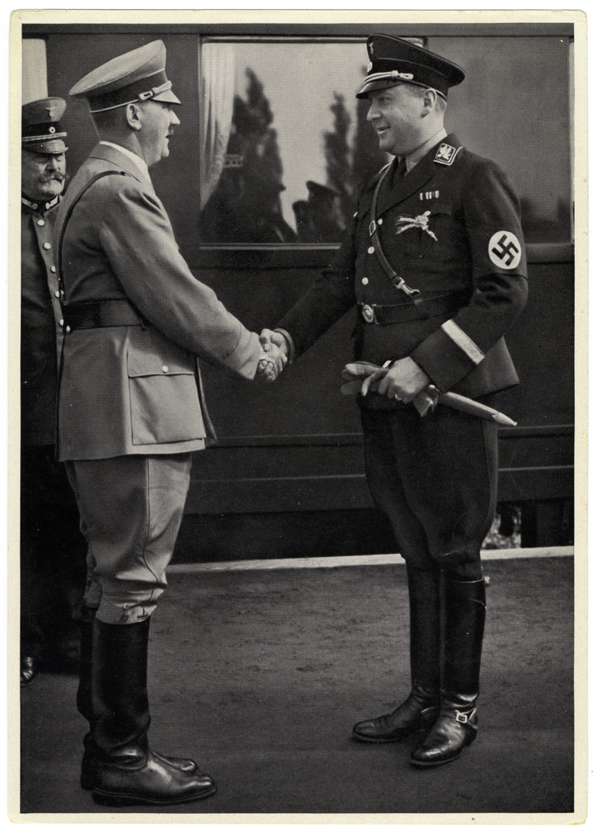"""Caption reads:  """"Minister Darre is welcomed by the Fuhrer on a Thanksgiving occasion""""  Richard Walther Darre (born Ricardo Walther Oscar Darre) was the Minister of Food and Agriculture in Germany from 1933-1942.  Paul von Hindenburg is pictured behind Hitler in this photo."""