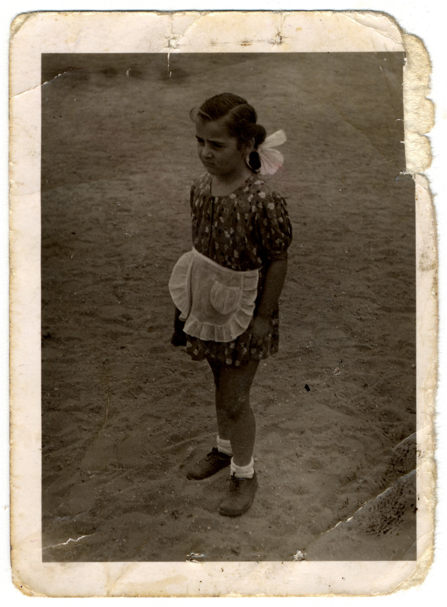 Four-year-old Agnes Biel poses on a street in Budapest in a dress and white apron.