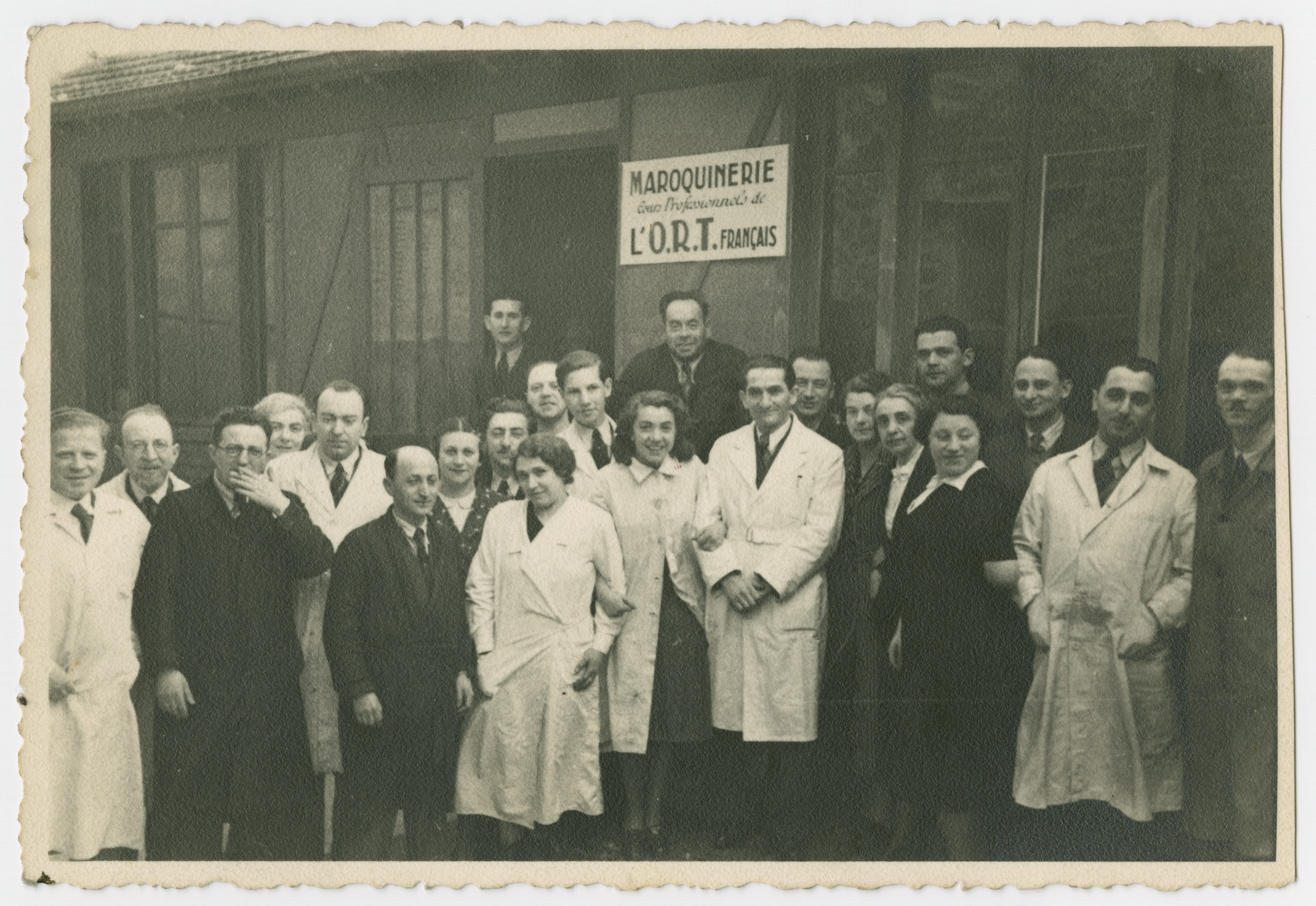 Group portrait of French survivors standing in front of an ORT leather-making workshop.