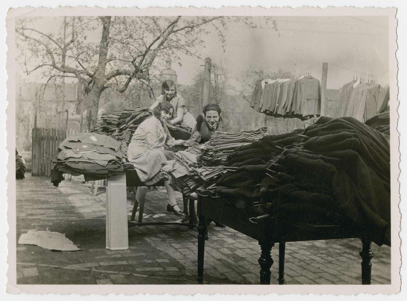The Kleeblatts air out clothing from their store during their spring cleaning.  Walter Kleeblatt is on the right.  His sister Edith is in the back, and Edith's friend Else is on the left.