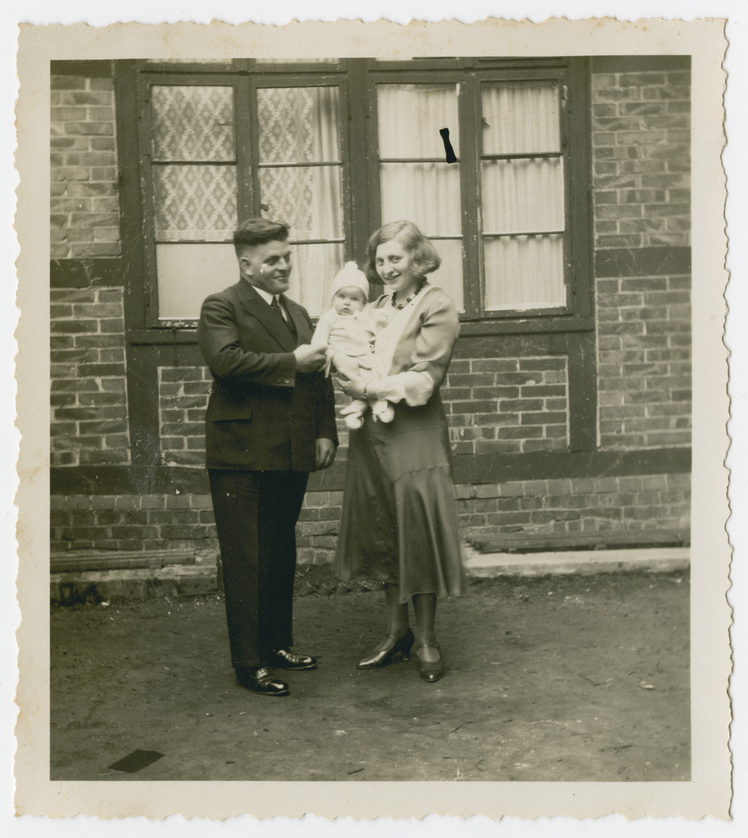 Julius and Else Gutheim stand outside a house with their infant daughter.