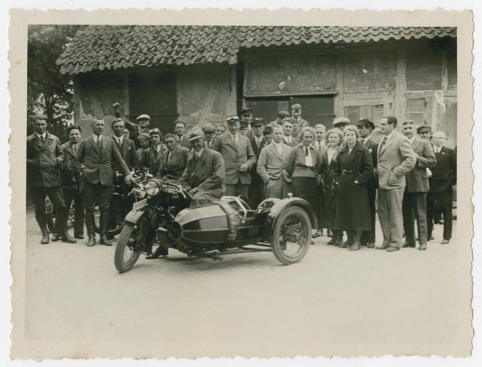 "Group portrait of members of a motorcycle club,  The original caption ""Fox Hunt"" refers to the orienteering game played by members of the club.  Walter Kleeblatt is pictured second from the left.  One of the members (back left) raises a fist in the communist ""Red Front"" greeting."