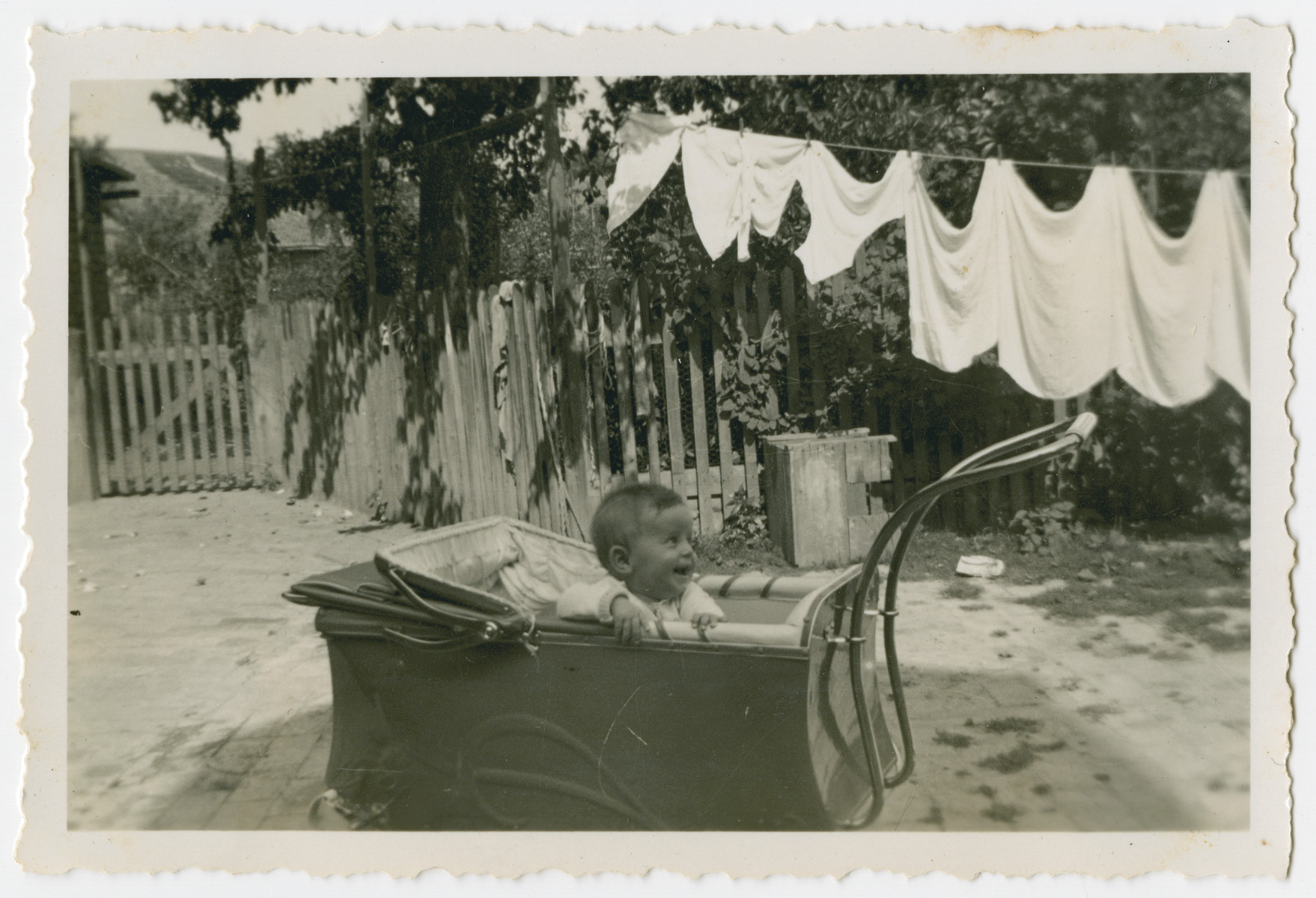 Werner Hirsch sits in his baby carriage in a yard in front of linens drying on a line.