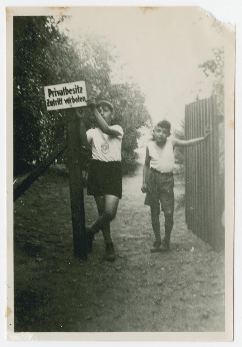 """Two boys from Haus Berta, a summer camp sponsored by the Reich Federation of Jewish Front Soldiers, pose by a sign that states """"Private Property: Entry Forbidden."""""""