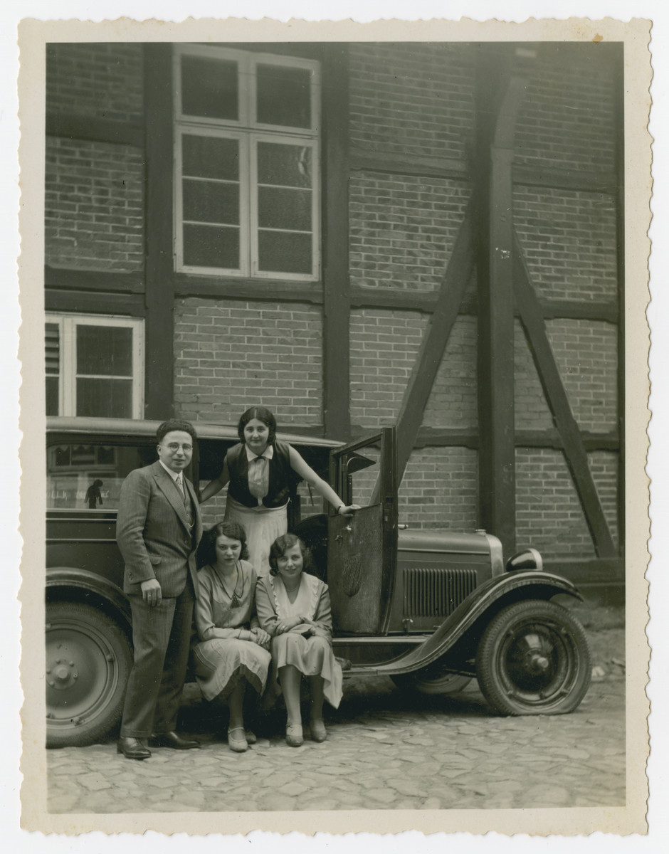 Young people pose next to their car prior to fixing its flat tire.  Pictured are Walter Kleeblatt (standing left), his girlfriend Gretel David (standing in the back), Erika Oschitzky (Gretel's close friend, seated left) and Walter;s sister Edith Kleeblatt (seated right).