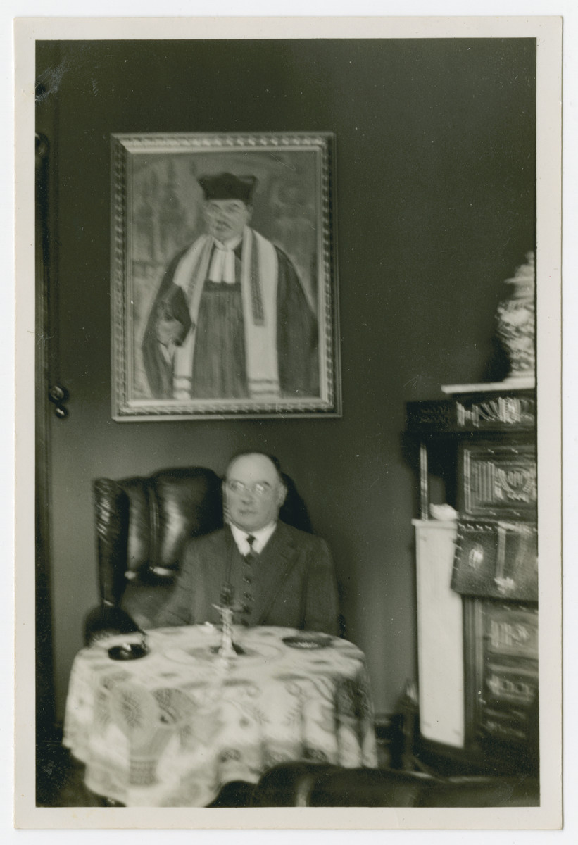Rabbi Moritz David, the rabbi of Bochum, sits at a table underneath his portrait.  David Moritz was born in 1875 in Gimbsheim in Worms and studied in Erlangen. In 1901 he was appointed as the first rabbi of the Jewish community of Bochum.  After serving briefly as rabbi in Dortmund, he immigrated to England in 1938 with the help of Leo Baeck.