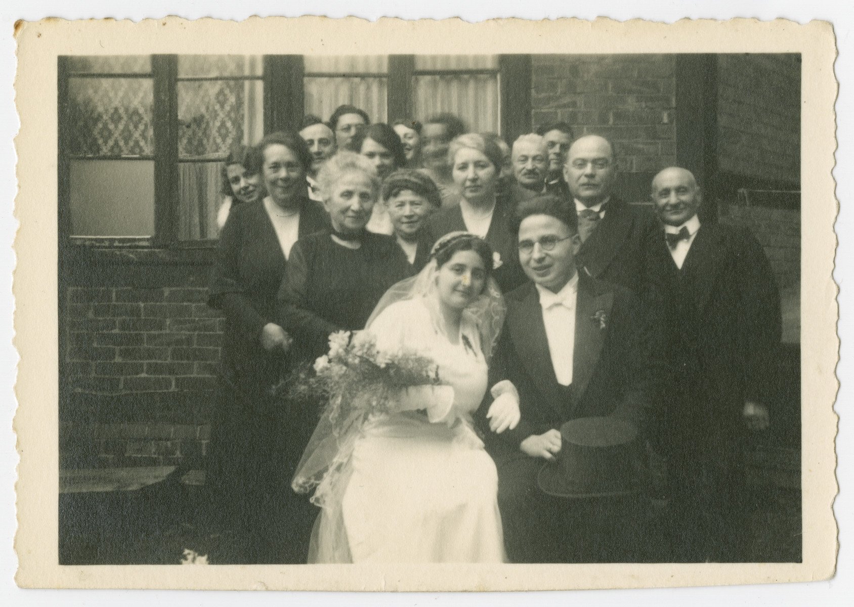 Family wedding portrait of Gretel David and Walter Kleeblatt.  Also pictured from left to right are  Helene Kleeblatt (left),  Paula David (middle), and next to her is Rabbi Moritz David, who performed the ceremony. Behind them are Adele Oschitzky (mother of Gretel's friend Erika), and Rosa Grueneberg, (the short lady whose head appears between Helene Kleeblatt and Paula David.  In the back are Edith Hirsch, Walter Hirsch, Erika Oschitzky and Gretel's aunt Flora Stern.  With the exception of Gretel and Walter Kleeblatt and Rabbi David, the rest of the people in the photo did not survive the Holocaust.