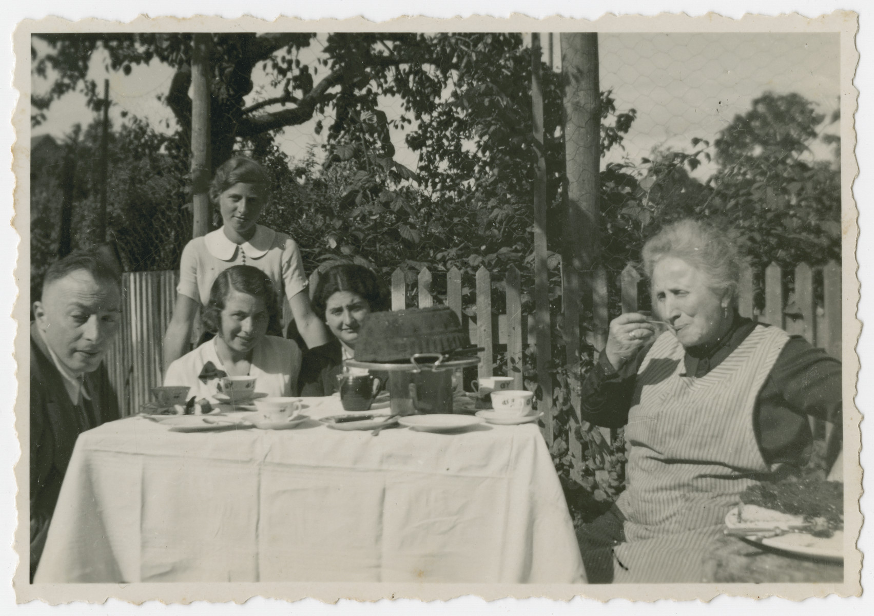 The Kleeblatt family celebrates Walter's birthday in their garden.  Pictured left to right are Arthur Kleeblatt, Edith Kleeblatt, Martha (a cousin standing behind her), Gretel David and Helene Kleeblatt. [Walter Kleeblatt is not pictured and probably took the picture.]