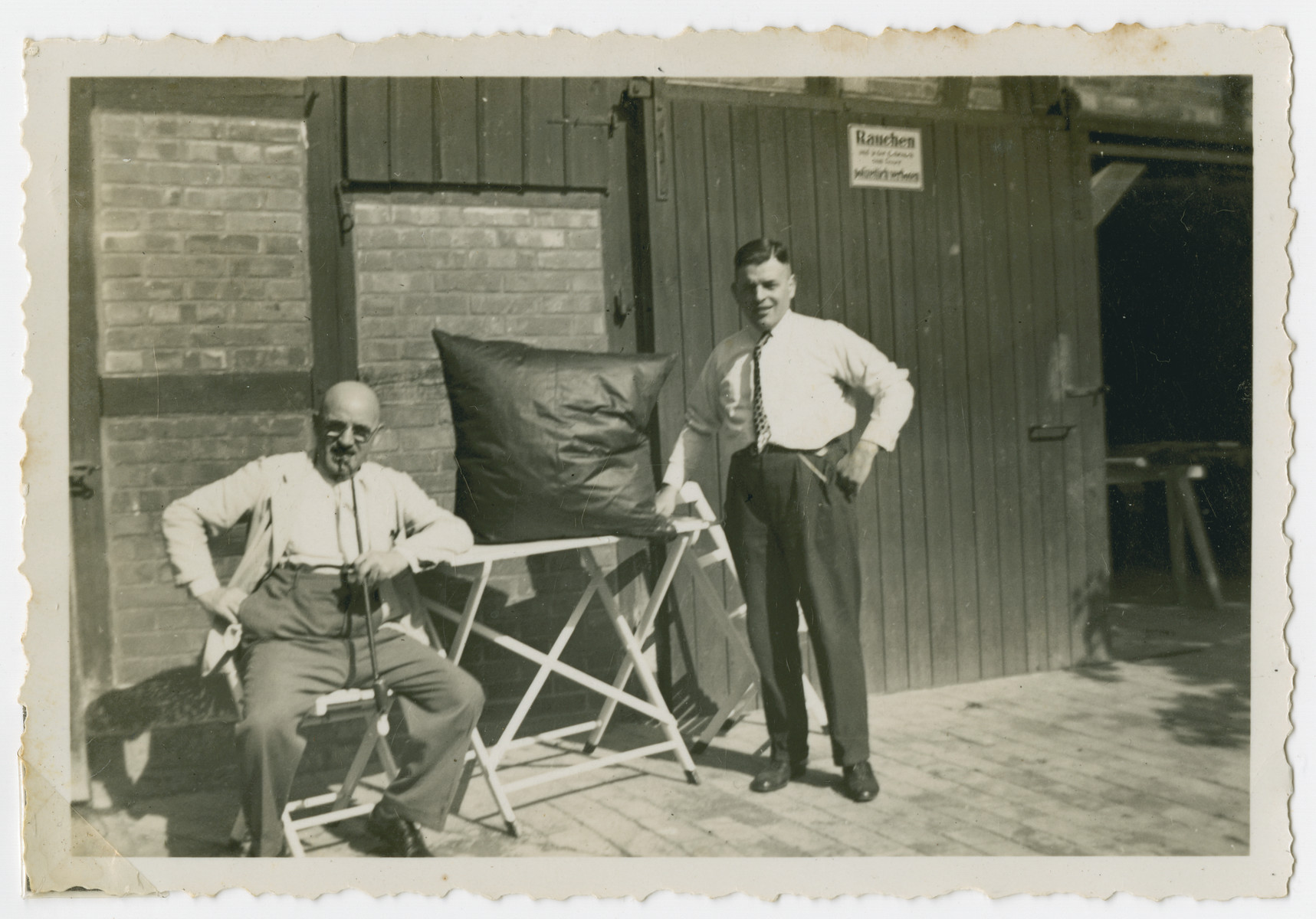 Julius Gutheim, co-owner of S. Kleeblatt,a dry-good store poses with Helene Kleeblatt's brother-in-law Louis Grueneberg.     They are in front of a former stable which was converted into a laundry for feather bedding.