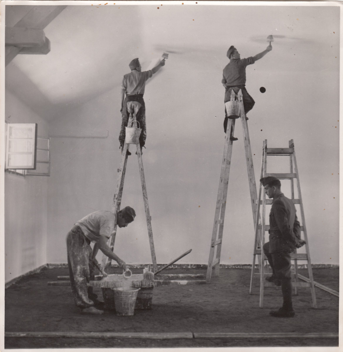 Members of a Jewish labor battalion paint the interior of a building in Hajduhadhaz.