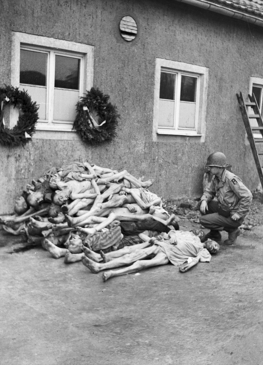Dr. William G. Birch crouches before corpses of concentration camp victims at Buchenwald.