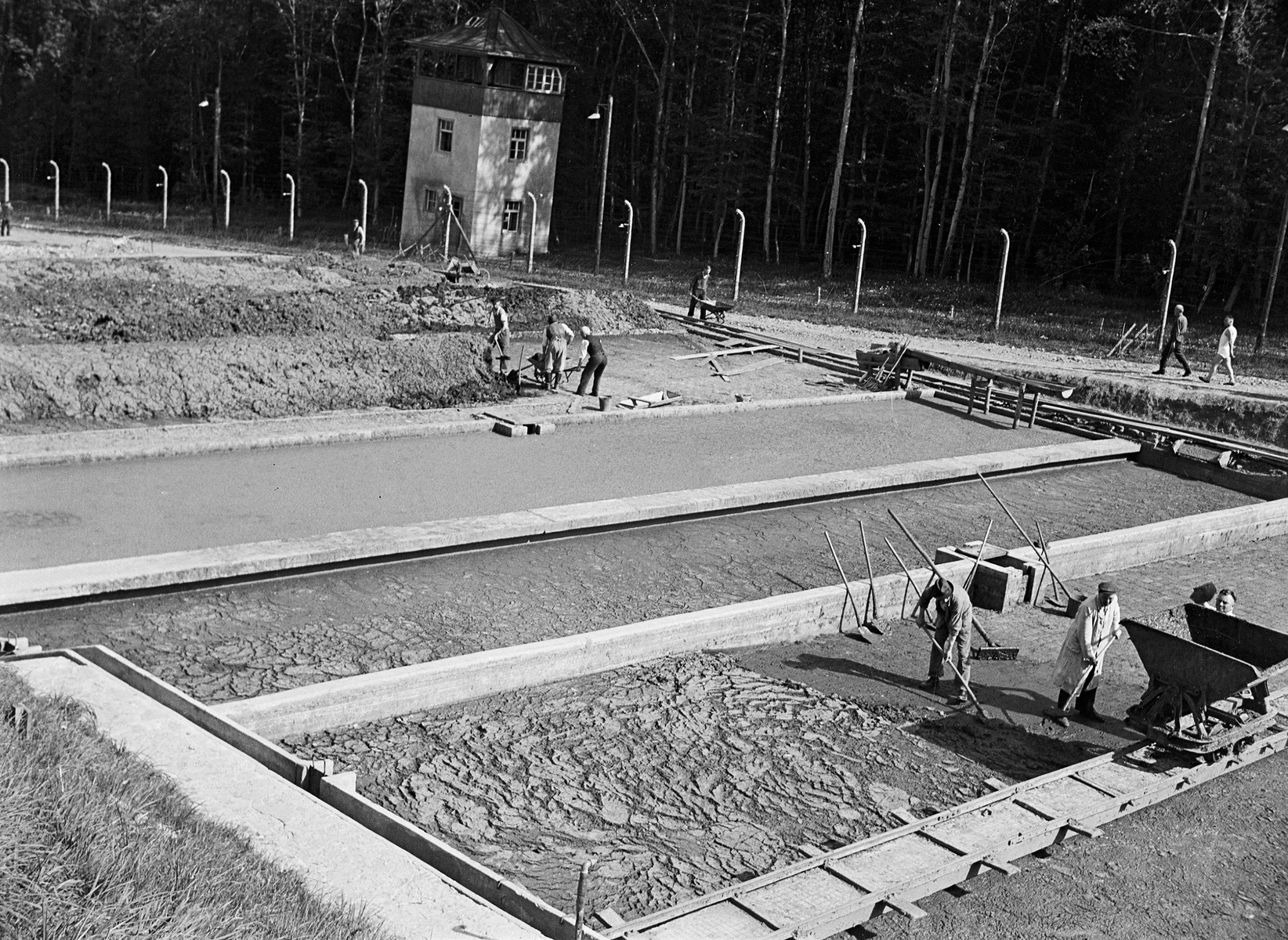 Waste disposal at Buchenwald.  The original caption identified those carrying out this work as former Nazis.