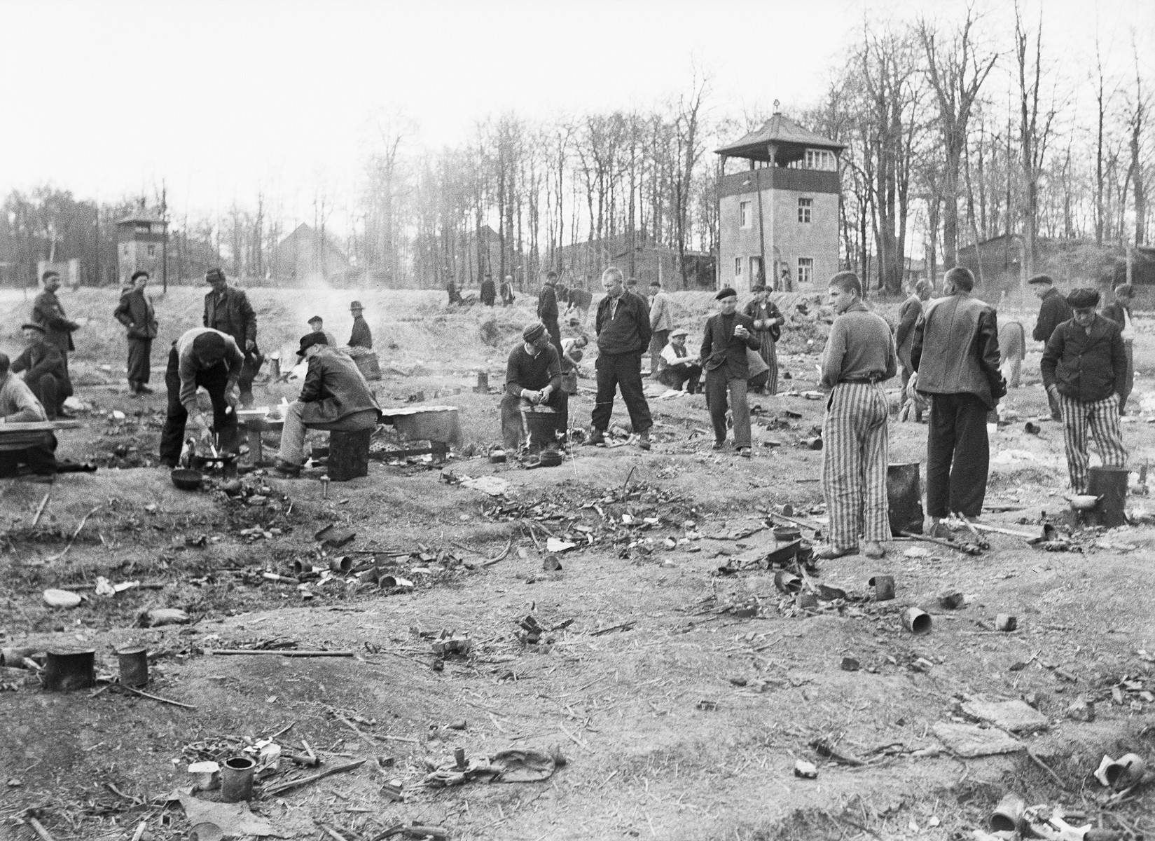 Recently liberated prisoners prepare food in the open at Buchenwald. Two guard towers are visible in the background.