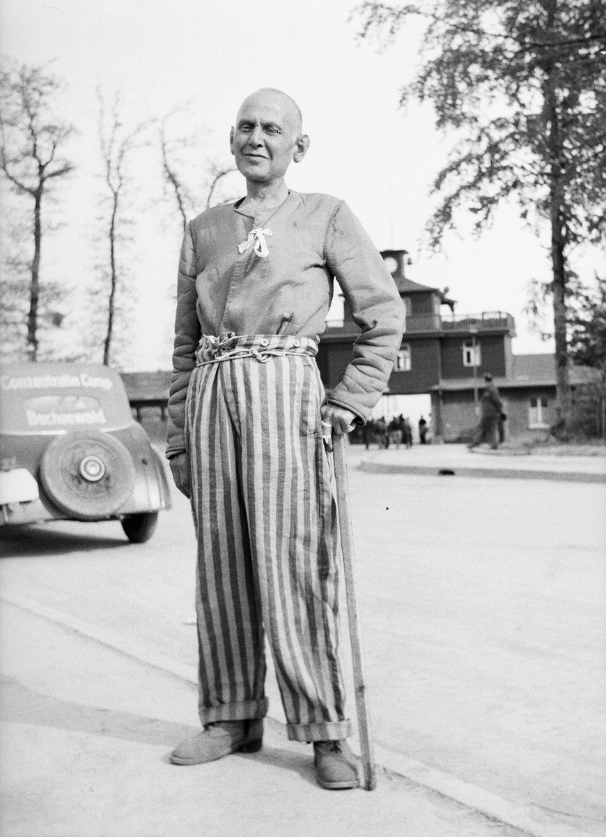 A survivor of the Buchenwald poses for a photograph before the gate of the camp after liberation.