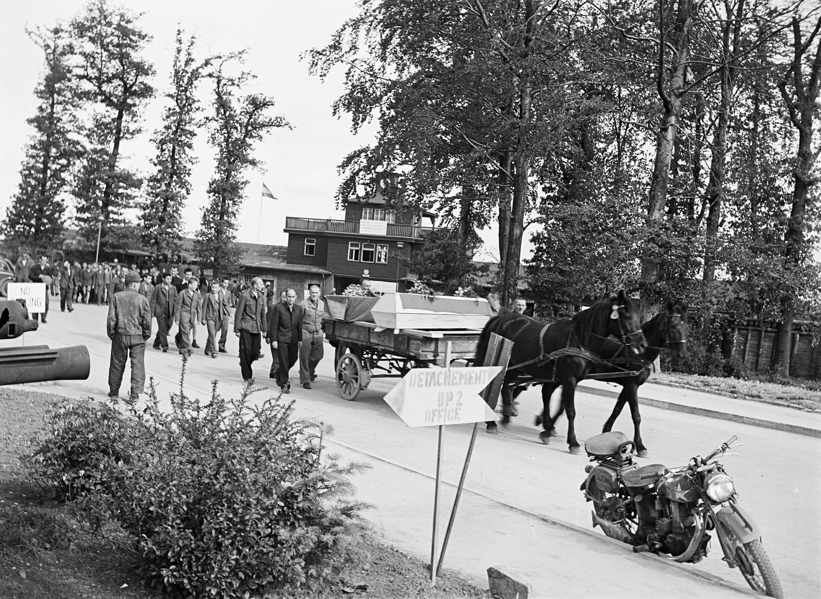 Former prisoners of Buchenwald follow a horse-drawn cart carrying caskets down a street outside the camp.