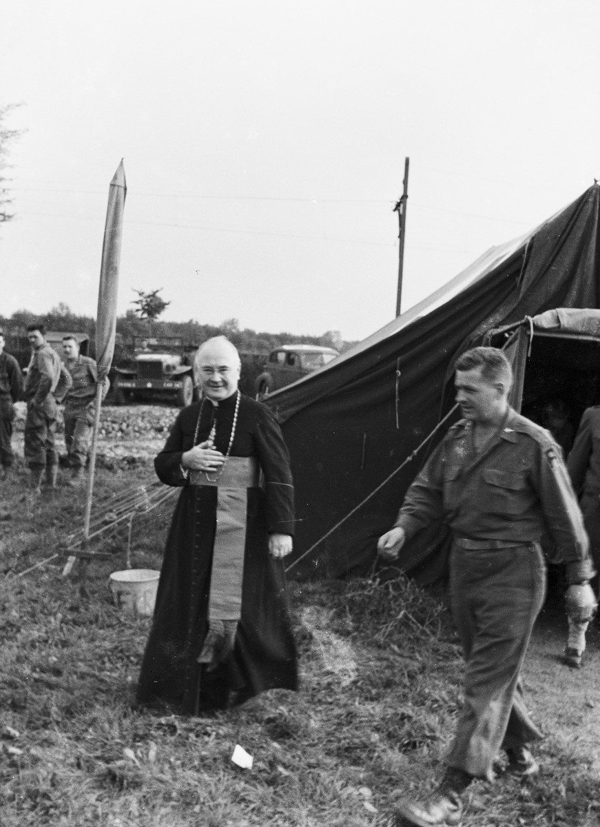 Archbishop and military vicar, Francis J. Spellman, is photographed exiting a U.S. Army tent, possibly after leading religious services for American troops.