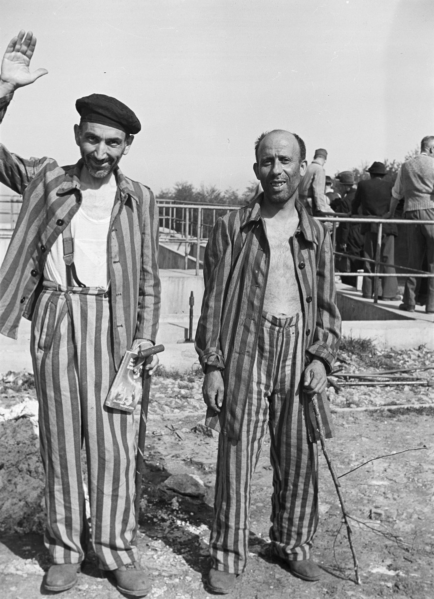Two survivors of Buchenwald pose for a photograph.    German civilians, likely brought in to Buchenwald to witness atrocities carried out in the camp, are visible in the background.
