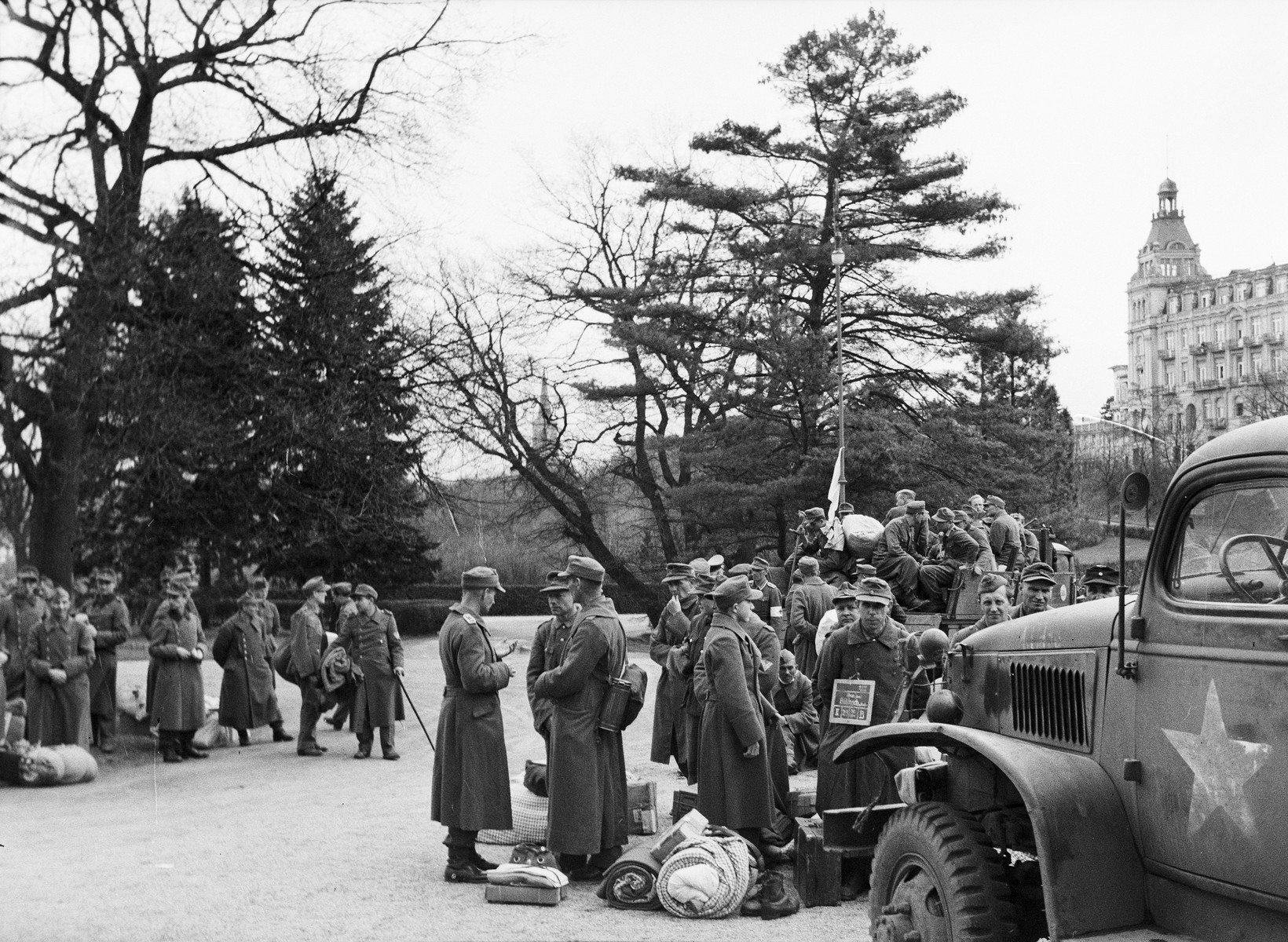 German POWs, who have been provided medical care by U.S. Army medical personnel of the 45th Evacuation Hospital, assemble before their transfer elsewhere.