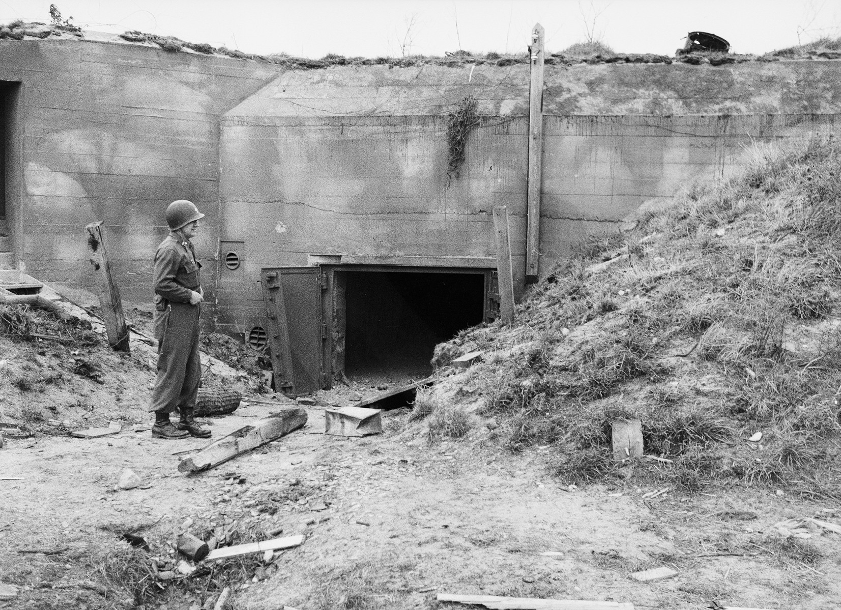 A medical officer with the U.S. Army's 45th Evacuation Hospital poses before the entrance of a fortified bunker after the Invasion of Normandy.